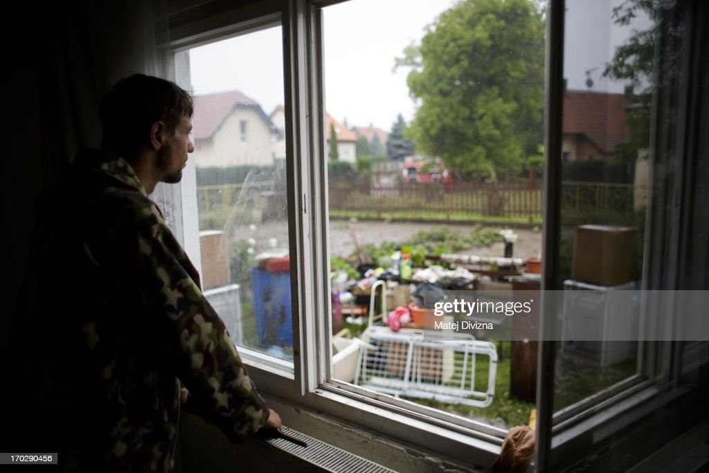 A local resident looks out a window at things from his home that were cleared out his house after flooding from Vltava River on June 10, 2013 in Luzec, Czech Republic. River levels in Czech Republic decreased and floodwaters have moved to Germany.