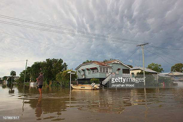 A local resident looks to the sky while standing in flood waters late in the afternoon on January 6 2011 in Rockhampton Australia Floodwaters peaked...