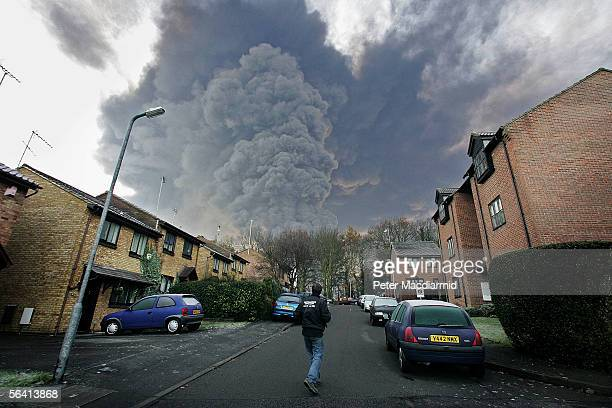 A local resident looks up as smoke rises from the a fire at the Buncefield fuel depot on December 11 2005 in Hemel Hemstead England The explosions...