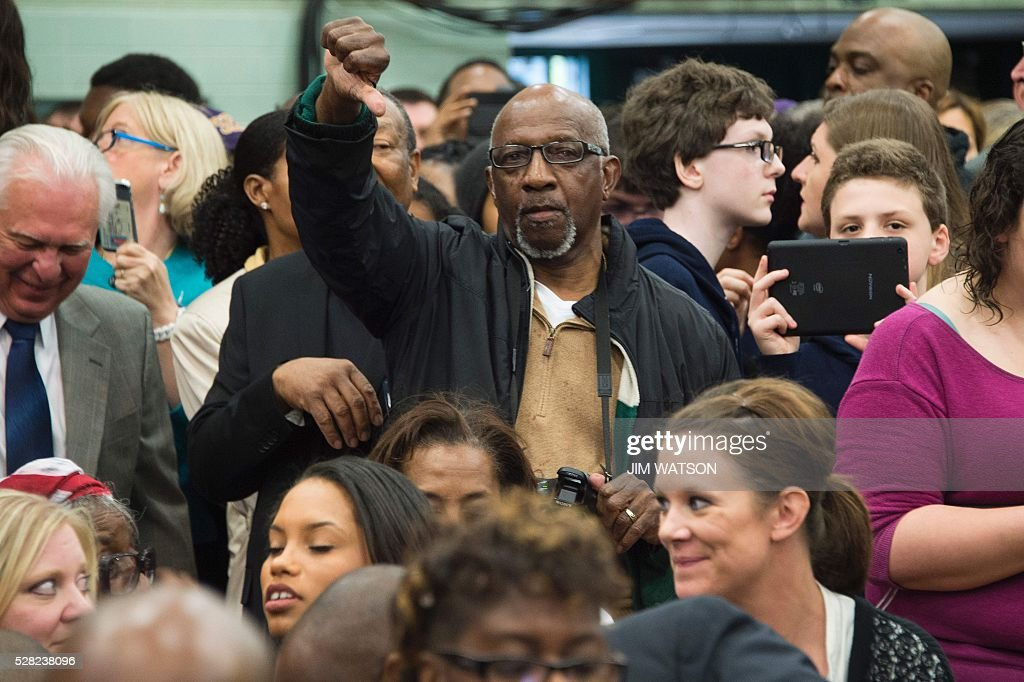 A local resident of Flint, Michigan gestures as Michigan Governor Rick Snyder speaks at Flint Northwestern High School in Flint, Michigan, May 4, 2016, where US President Barack Obama met with locals for a neighborhood roundtable on the drinking water crisis. / AFP / Jim Watson