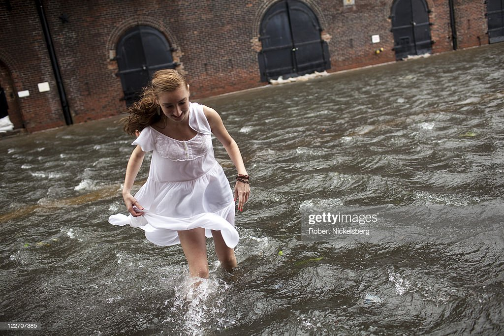 A local resident of Red Hook, Betty Walsh, crosses a flooded street in Red Hook August 28, 2011 in the Brooklyn borough of New York City. While Hurricane Irene has now been downgraded to a tropical storm, it has knocked out power to more than 3 million people and is attributed to 15 deaths as it travels up the Eastern seaboard.