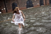 A local resident of Red Hook Betty Walsh crosses a flooded street in Red Hook August 28 2011 in the Brooklyn borough of New York City While Hurricane...