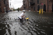 A local resident of Red Hook Franklin Mount crosses a flooded street on his bicycle in Red Hook August 28 2011 in the Brooklyn borough of New York...
