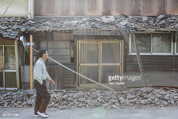 A local resident passes by collapsed house after an earthquake on April 15 2016 in Mashiki Kumamoto Japan At least nine people have died in a...