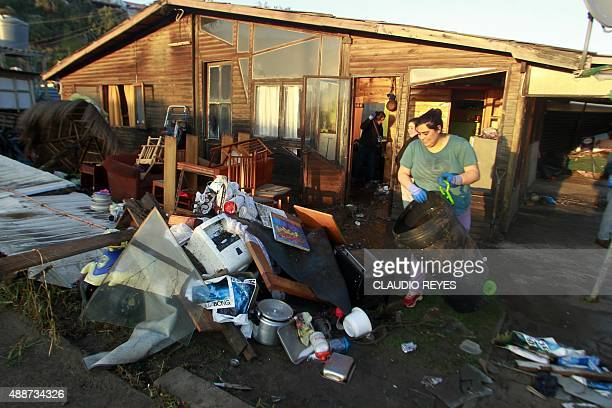 A local resident puts out her belongings to dry outside her home in Concon some 110 km northwest of Santiago on September 17 2015 hit by an...