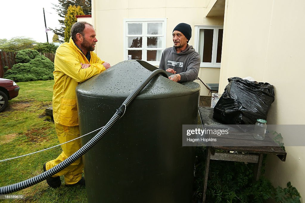 Local resident Ricky McLeod (R) fills his temporary water tank with fresh water on October 12, 2013 in Raetihi, New Zealand. Work has begun to flush a stream contaminated by a large diesel spill at Tongariro National Park. A tank from the Turoa Ski Field has leaked 15,000 litres of diesel into the Makotuku stream.