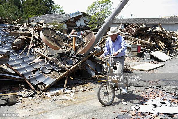 A local resident rides a bicycle among destroyed houses on April 20 2016 in Mashiki near Kumamoto Japan As of 20th of April 48 people were confirmed...