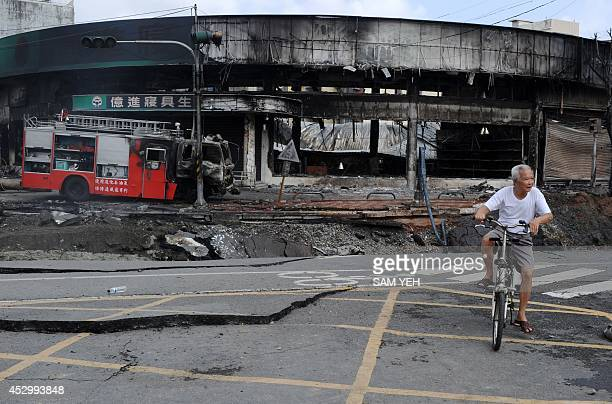 A local resident rides past the site of a gas explosion in the southern Taiwan city of Kaohsiung on August 1 2014 A series of powerful gas blasts...