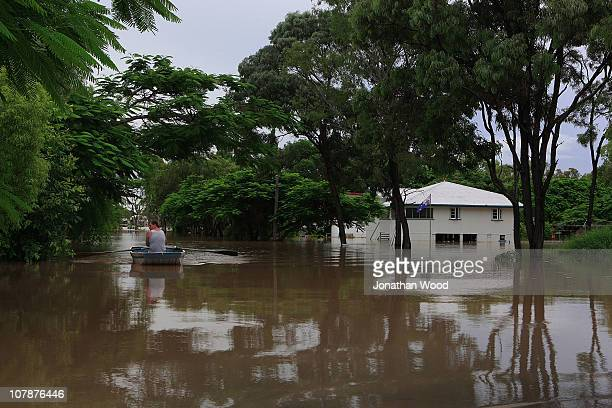 A local resident rows from his home through flood waters on January 5 2011 in Rockhampton Australia All eyes are on the central Queensland city of...