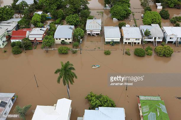 A local resident rows through flood waters which have covered a suburban street on January 6 2011 in Rockhampton Australia Floodwaters peaked at 92...