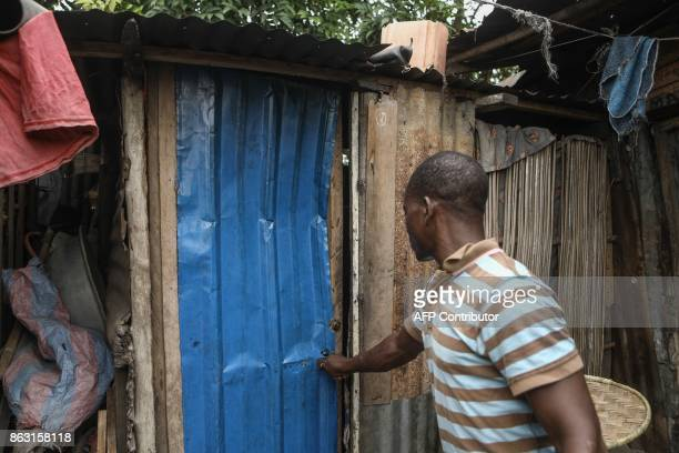 A local resident shows a broken door after police allegedly stormed the neighborhood during demonstrations looking for protesters and broke down...