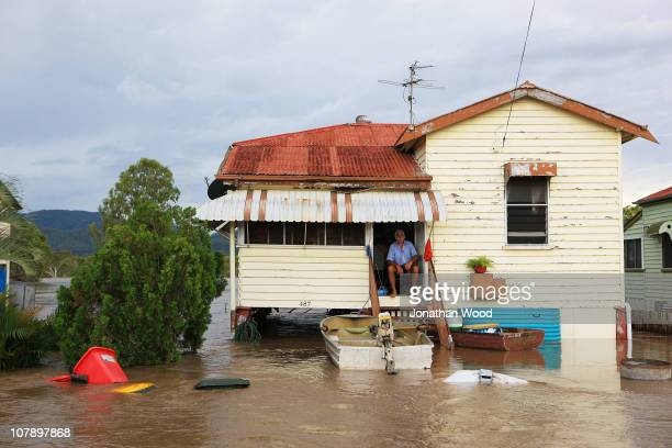 A local resident sits in his home surrounded by flood waters on January 6 2011 in Rockhampton Australia Floodwaters peaked at 92 metres yesterday in...