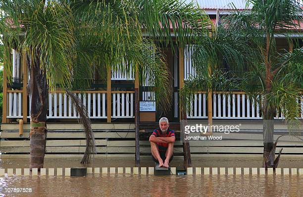 A local resident sits outside his home surrounded by flood waters on January 6 2011 in Rockhampton AustraliaFloodwaters peaked at 92 metres yesterday...
