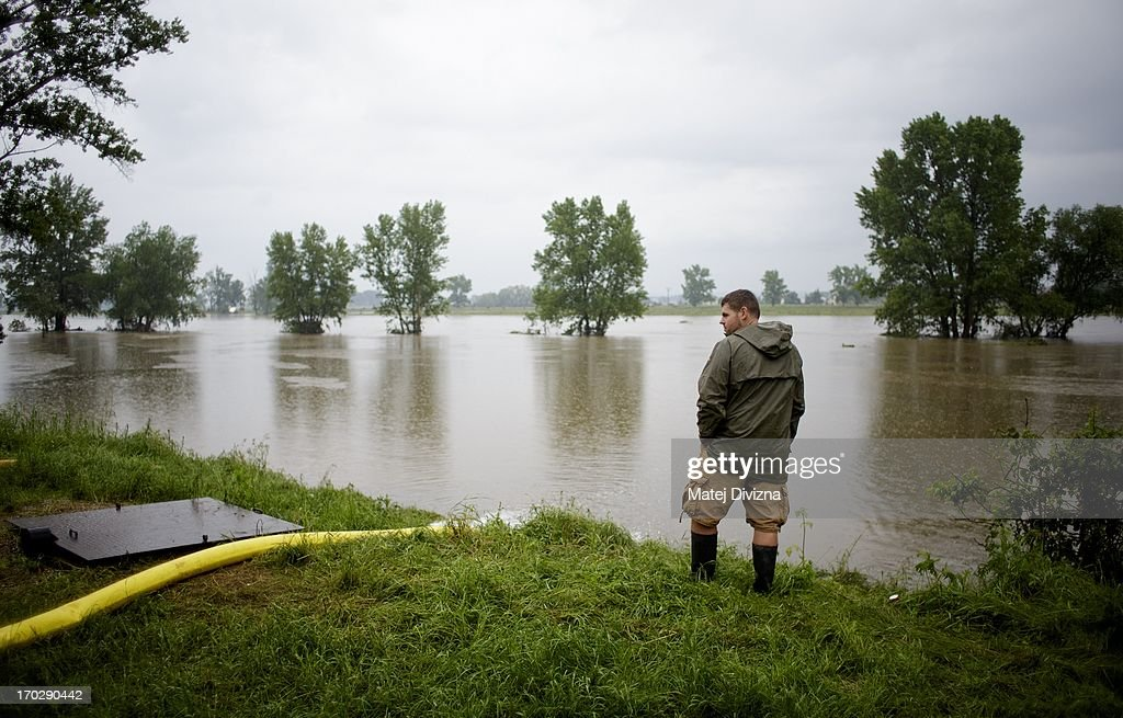 A local resident stands at teh edge of the flooded Vltava River during a rainy day on June 10, 2013 in Luzec, Czech Republic. As river levels in Czech Republic decrease expectations of flooding increase in Northern Germany triggering more evacuations.