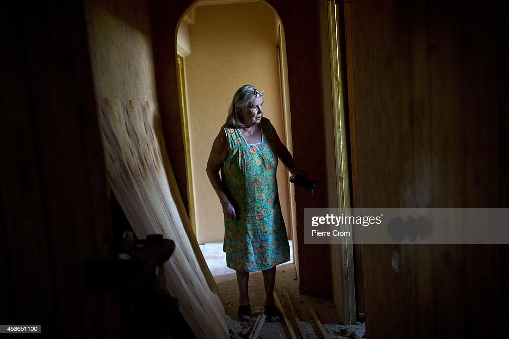 A local resident stands in her damaged appartment which was hit by shelling in the Oktoberski district, one of the most shelled areas of the city considered a 'no man's land' between pro-Russian and Ukranian positions on August 15, 2014 in Donestk, Ukraine. A Russian aid convoy has reached the Ukranian border and is being inspected by Ukrainian border guards before it will be allowed to enter into the country. Meanwhile Ukraine say their forces have come under more shelling from Russia in what reports suggest is an escalation in fighting between the two countries.
