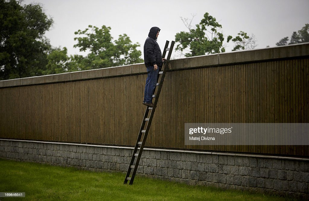 A local resident stands on a ladder as he looks at over a barrier at the flooded Vltava river in the Zbraslav district on June 3, 2013 in Prague, Czech Republic. After days of heavy rainfall rivers have flooded in the centre of Prague causing evacuations and the risk or serious damage to the historic city. Three persons have been killed and several are missing across the country as rivers continue to rise throughout western and southern Bohemia.