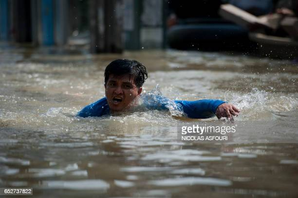 A local resident swims in floodwaters after a mud and sandbag wall collapsed in Bang Bua Thong in Nonthaburi province suburban Bangkok on October 19...