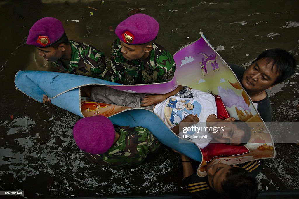 Local resident Syamsuri is evacuated by Indonesian Army as major floods hit North Jakarta on January 20, 2013 in Jakarta, Indonesia. The death toll has risen to at least 21since severe flooding struck the city on January 17. The US has offrered US$150,000 (Rp 1.44 billion) in aid.