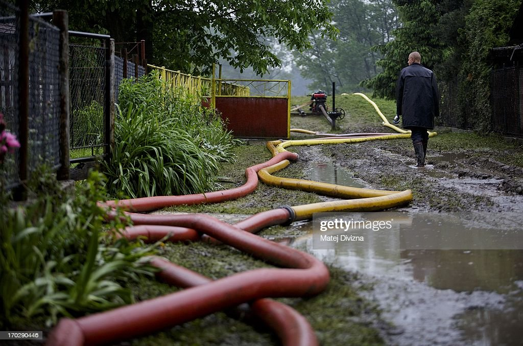 A local resident walks along hoses during a rainy day after flooding from Vltava River on June 10, 2013 in Luzec, Czech Republic. As river levels in Czech Republic decrease expectations of flooding increase in Northern Germany triggering more evacuations.