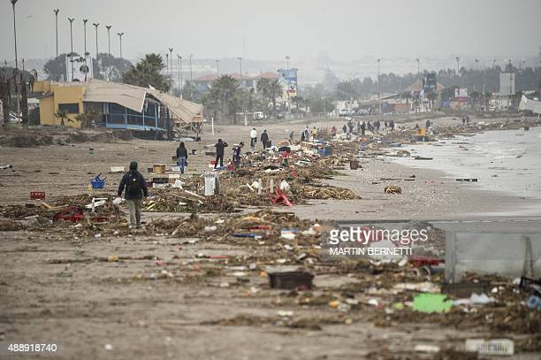 Local resident walks amid of the debris left on the beach by the tsunami that ensued an 83 quake that left 12 people dead and five more missing in...