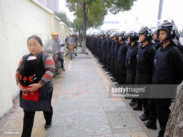 A local resident walks past policemen in line at the place the meeting to mourn over the suspectedly killed in clash during the protest against the...