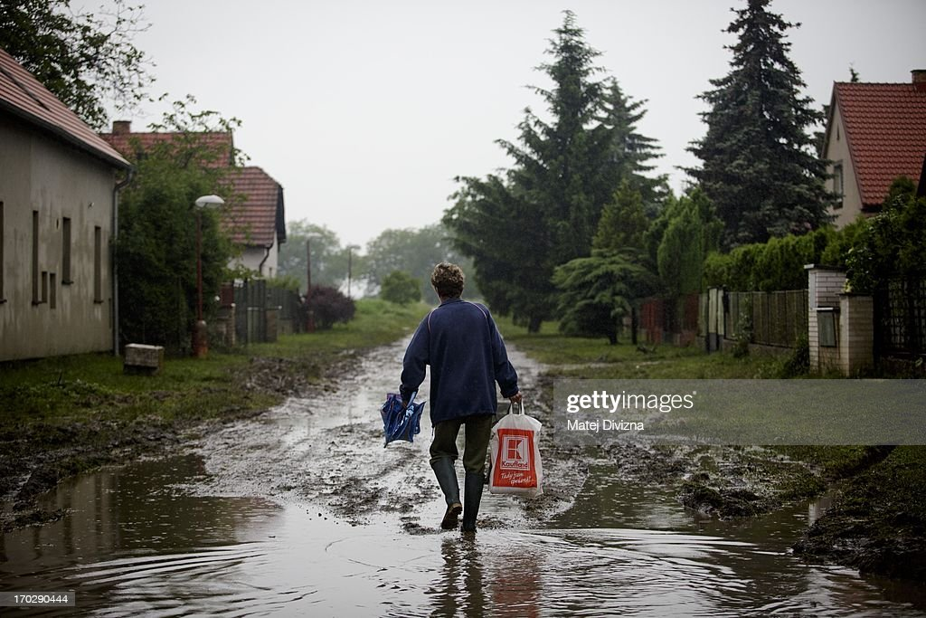 A local resident walks through a puddle during a rainy day after flooding from Vltava river on June 10, 2013 in Luzec, Czech Republic. As river levels in Czech Republic decrease expectations of flooding increase in Northern Germany triggering more evacuations.