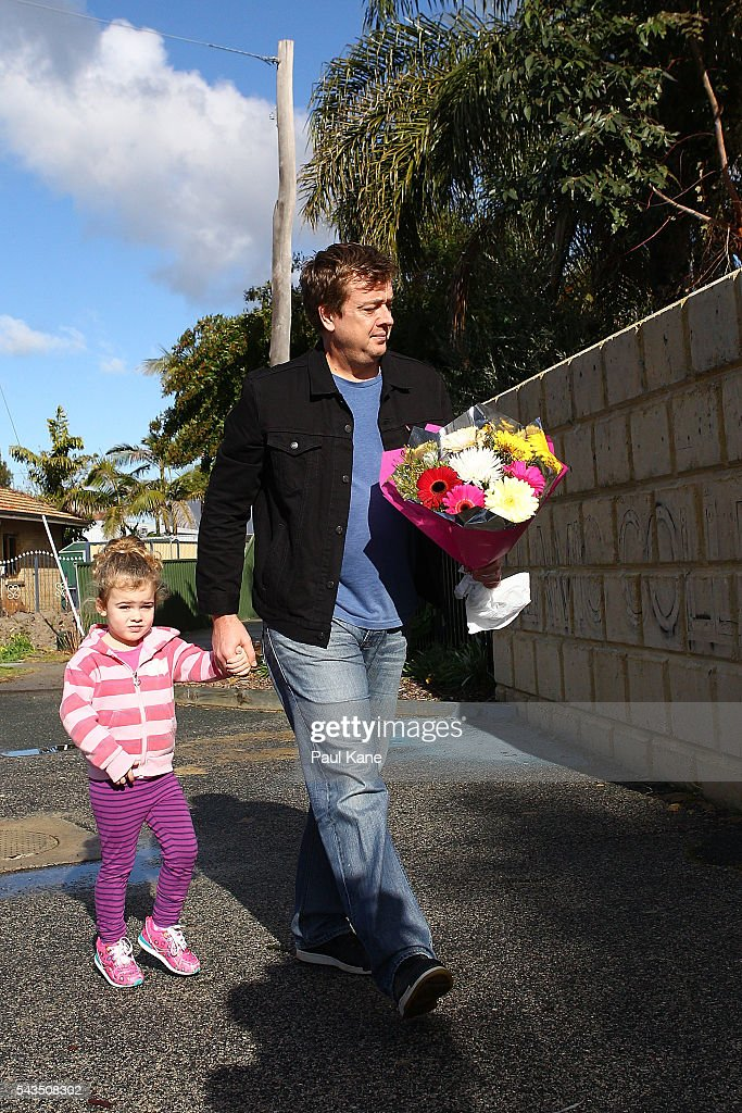 A local resident walks with his daughter to place a floral tribute at the gates of the Thornlie Australian Islamic College and Mosque on June 29, 2016 in Perth, Australia. Police are investigating a firebomb attack which occurred last night at the Thornlie Mosque. No one was injured in the attack which took place during evening prayers.
