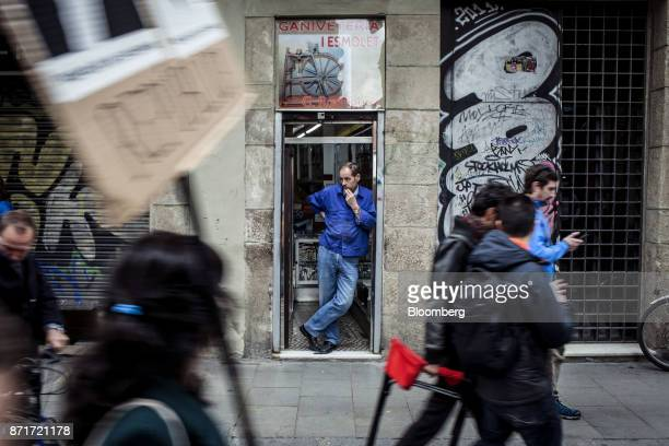 A local resident watches as protesters march through the Raval neighbourhood during a regional strike called by proindependence union in Barcelona...
