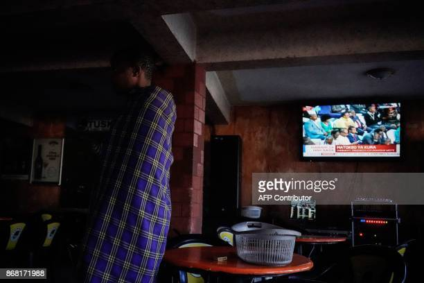 A local resident watches live broadcast of the announcement of the reelection's result by Kenya's Independent Electoral and Boundaries Commission...