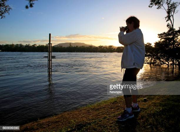 ROCKHAMPTON QLD A local resident watches the rising floodwaters in Rockhampton Queensland after the Fitzroy River burst its banks in the aftermath of...