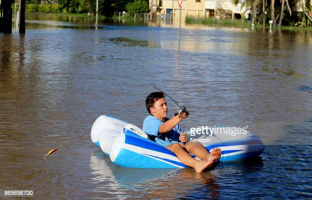 ROCKHAMPTON QLD Local resident Zammyth fishing from his dinghy in floodwaters at Depot Hill in Rockhampton Queensland after the Fitzroy River burst...