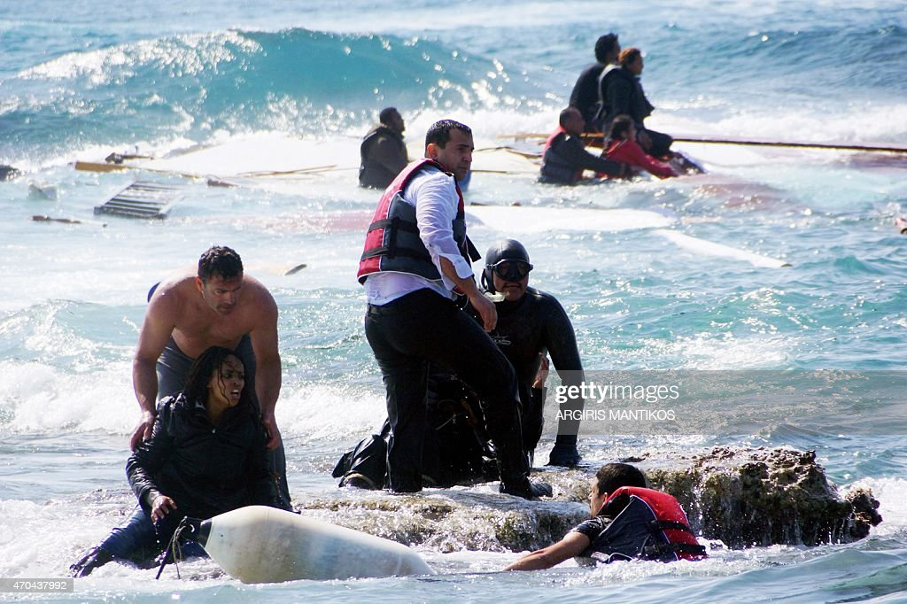 Local residents and rescue workers help a migrant woman after a boat carrying migrants sank off the island of Rhodes southeastern Greece on April 20...