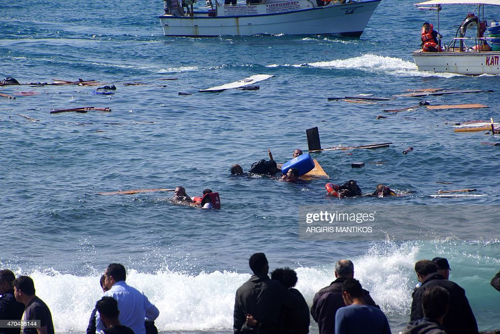 Local residents and rescue workers try to help migrants after their boat sank off the island of Rhodes southeastern Greece on April 20 2015 At least...