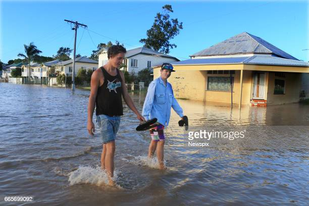 ROCKHAMPTON QLD Local residents Brodie Govaars and Thomas Weldon wade through floodwaters at Depot Hill in Rockhampton Queensland after the Fitzroy...