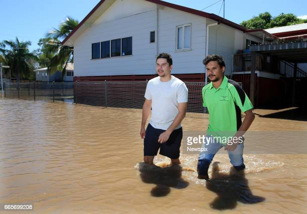 ROCKHAMPTON QLD Local residents Cameron Gooda and his brother Peter Gooda wade through floodwaters at Depot Hill in Rockhampton Queensland after the...