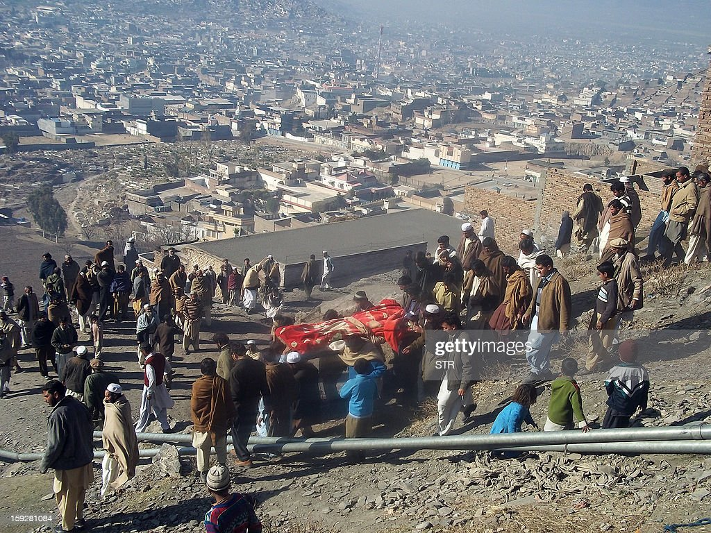 Local residents carry the coffin of a bomb blast victim during a funeral in Mingora, the main town in the district, on January 11, 2013. An explosion at a religious gathering in Pakistan's northwestern Swat valley that killed 22 people and wounded more than 80 was caused by a bomb, officials said Friday. AFP PHOTO/STR