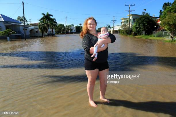 ROCKHAMPTON QLD Local residents Chloe Clements with her daughter Lily Rose wade through floodwaters at Depot Hill in Rockhampton Queensland after the...