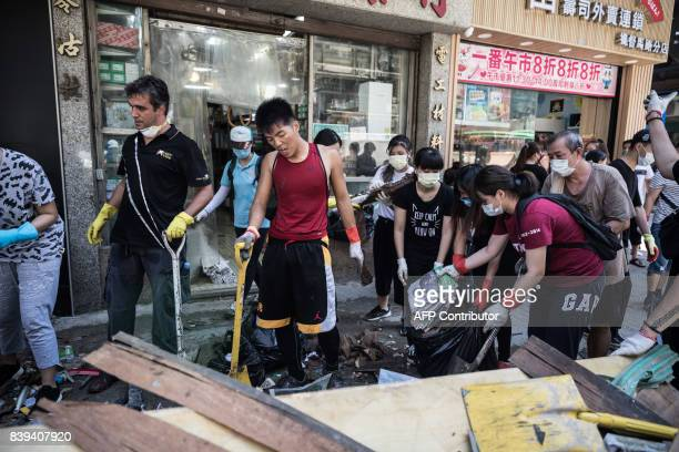 Local residents clean debris and rubbish on a street in the aftermath of Typhoon Hato in Macau on August 26 2017 The Chinese army on August 25 joined...