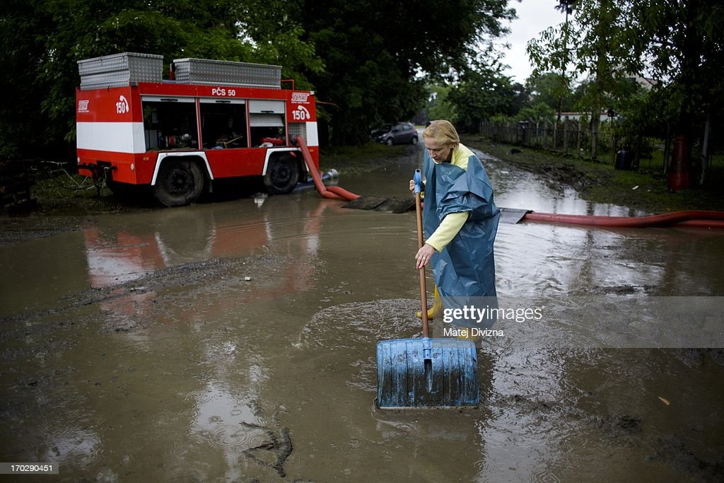 A local residents cleans up in front of her house during a ainy day after flooding from Vltava River on June 10, 2013 in Luzec, Czech Republic. As river levels in Czech Republic decrease expectations of flooding increase in Northern Germany triggering more evacuations.