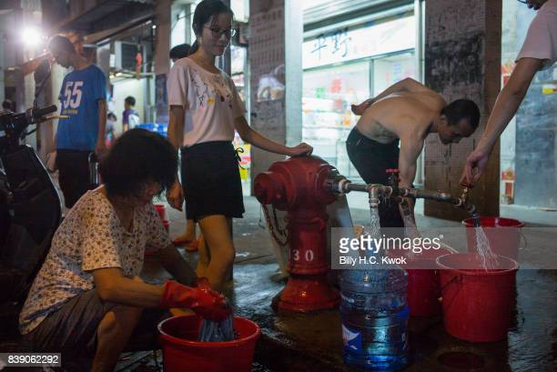 Local residents collect water from a public water tab after water pipes have been broken by Typhoon Hato in Macao on August 23 2017 in Macau China...