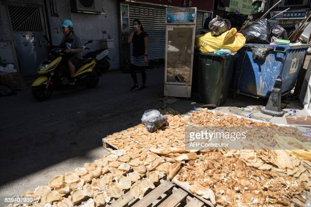 Local residents commute past dried seafood goods left in the sun to dry next to piles of garbage in the aftermath of Typhoon Hato in Macau on August...
