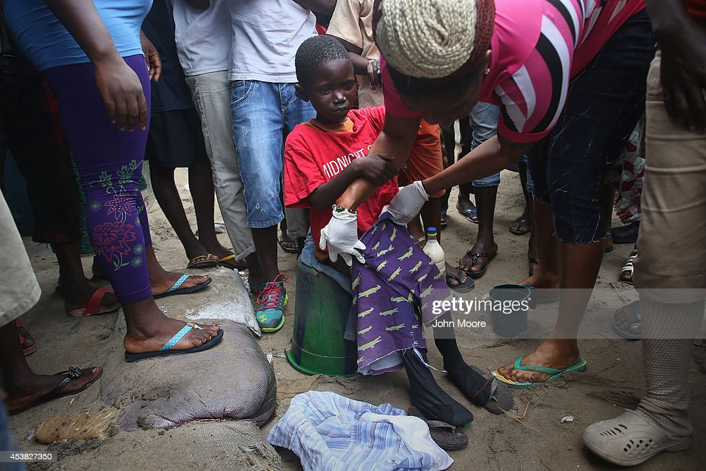 Local residents dress a sick Saah Exco, 10, after bathing him in a back alley of the West Point slum on August 19, 2014 in Monrovia, Liberia. According to communitey organizer John Saah Mbayoh, Saah's mother died of suspected but untested Ebola in West Point before he was brought to the isolation center the evening of August 13. He came with his brother, Tamba, 6, aunt Ma Hawa, and cousins. His brother died on August 15 at the center. Saah fled the center the August 15 with several other patients before it was overrun on August 16 by a mob. Once out in the neighborhood, he was not sheltered, as he had suspected Ebola - so he has been sleeping outside. Residents reportedly began giving him medication, a drip and oral rehydration liquids today. The whereabouts and condition of his aunt and cousins, who left the facility when it was overran by the crowd, is still unknown at this time. The Ebola virus has killed more than 1,000 people in four African nations, more in Liberia than any other country.