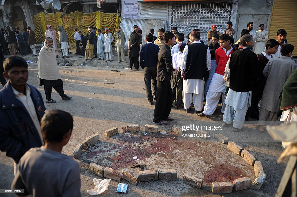 Local residents gather at the site of an overnight suicide bomb attack on minority Shiite Muslims procession in Rawalpindi on November 22, 2012. A suicide bomber struck a night-time Shiite march in Pakistan, in the bloodiest attack of a day of violence that left at least 28 people dead as Islamic leaders gathered for a rare summit in Islamabad. Police in the garrison city of Rawalpindi near the capital said the attack on the procession of minority Shiite Muslims killed at least 16 people, after the suicide bomber blew himself up when he was stopped for a security check. AFP PHOTO/Aamir QURESHI