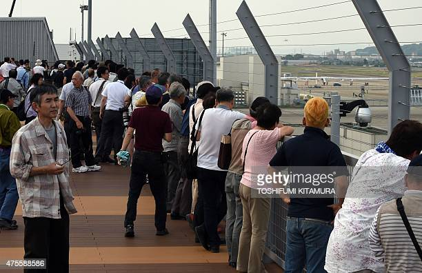 Local residents gather on an observation deck to watch the solarpowered airplane Solar Impulse 2 parking at the Nagoya airport in Nagoya on June 2...