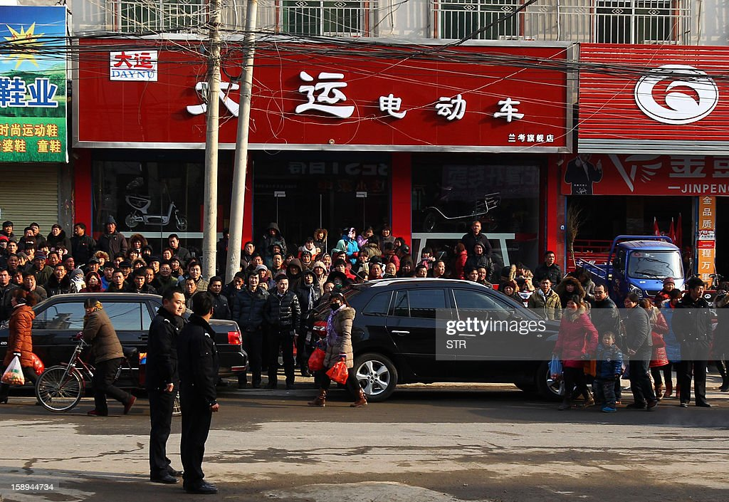 Local residents gather to watch as rescuers and inspectors check a private orphanage after a fire swept through the home in Lankao, in central China's Henan province on January 4, 2013. Seven children died and another was injured in the accident, local government and state media said. CHINA