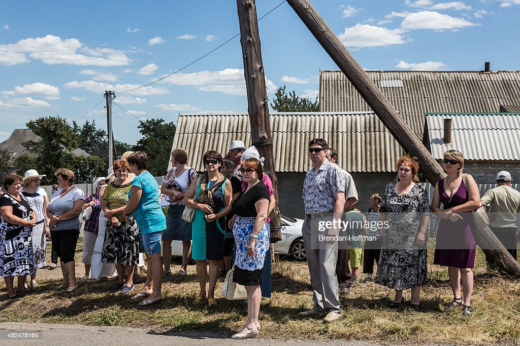 Local residents gather to watch as the bodies of victims of Malaysia Airlines flight MH17 are removed from the scene of the crash on July 21, 2014 in Grabovo, Ukraine. Malaysia Airlines flight MH17 was travelling from Amsterdam to Kuala Lumpur when it crashed killing all 298 on board including 80 children. The aircraft was allegedly shot down by a missile and investigations continue over the perpetrators of the attack.