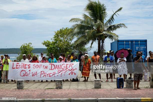 Local residents hold a banner reading 'the islands are in danger who's going to pay' during a demonstration against oil pollution in the town of We...