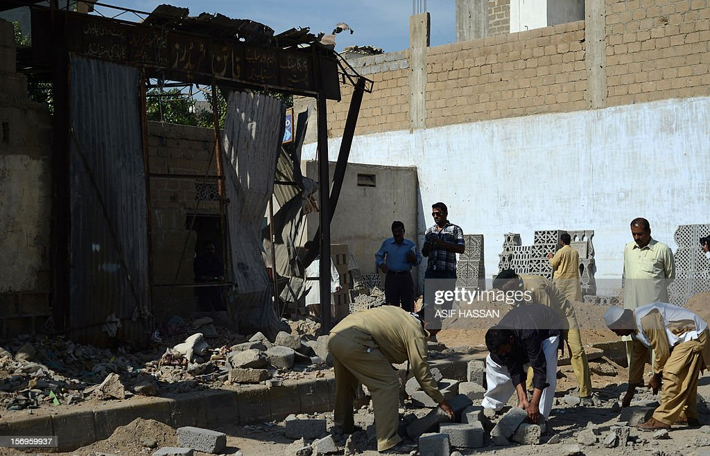 Local residents inspect the site of a bomb explosion in the port city of Karachi on Novmeber 26, 2012. A bomb attack killed a labourer and wounded four passers-by, officials said. The blast was detonated by a mobile phone and authorities said they believed it had been planted to target a procession of Shiite Muslims who had been scheduled to pass through the area in recent days. AFP PHOTO/Asif HASSAN