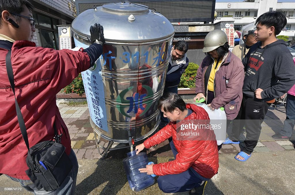 Local residents line up for water as the earthquake damaged water pipes near the collapsed Wei Kuan complex building in Tainan, southern Taiwan, on February 7, 2016. Rescuers raced on February 7 to free more than 120 people buried under the rubble of an apartment complex felled by an earthquake in southern Taiwan that left 24 confirmed dead, as an investigation began into the collapse. AFP PHOTO / Sam Yeh / AFP / SAM YEH