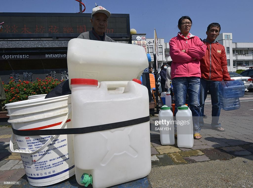Local residents line up for water following the disruption of water supply lines near the collapsed Wei Kuan complex building on the second day of rescue operations following a 6.4 magnitude earthquake in southern Taiwan's city of Tainan on February 7, 2016. Rescuers raced against time February 7 to free more than 100 people buried beneath the rubble of apartment blocks felled by an earthquake in southern Taiwan that left 19 dead, as an investigation was launched into the building collapse. AFP PHOTO / Sam Yeh / AFP / SAM YEH